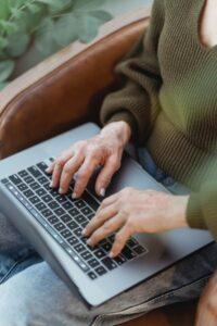 Persoon die een laptop op schoot gebruikt