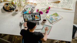 Persoon die op iPad aan bureau ontwerpt