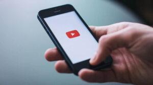 Persoon die telefoon vasthoudt met YouTube open