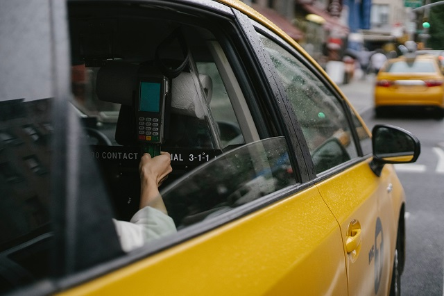 Passagier die een creditcardverwerkingsmachine gebruikt in een gele taxicabine