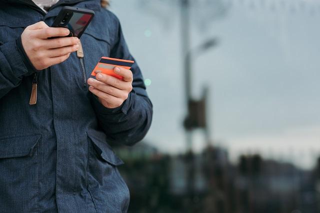 Persoon die creditcard gebruikt met zijn mobiele telefoon