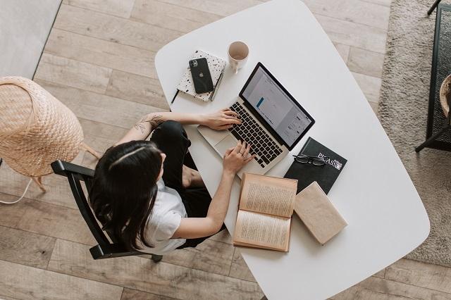 Vrouw die op een laptop werkt met een open boek in de buurt