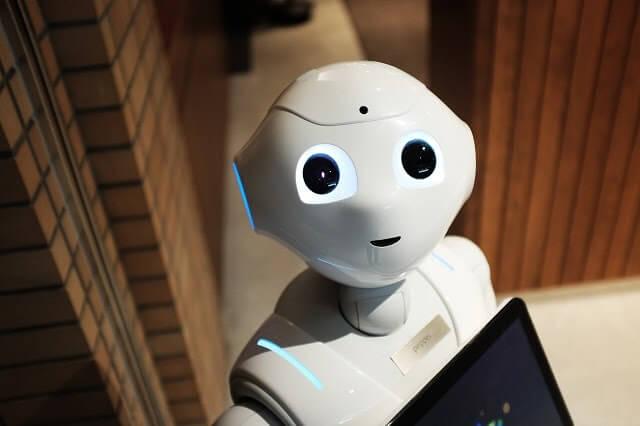 Robot die opkijkt van achter een computer