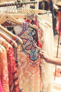 Persoon die door een kledingrek kijkt