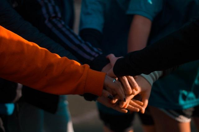 Groep mensen met gestapelde handen