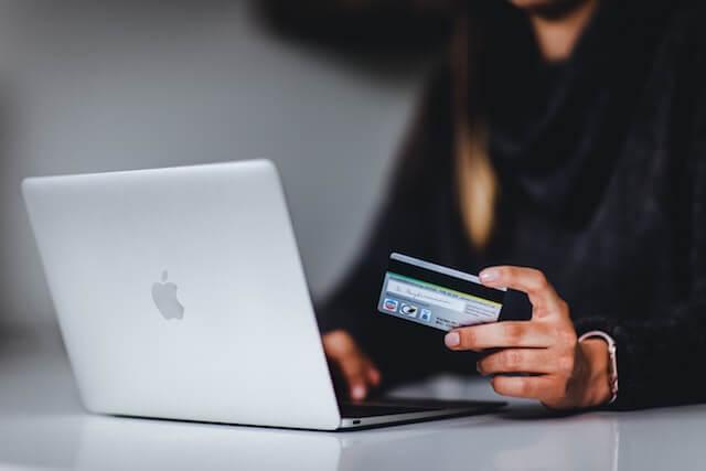 Persoon op de computer met een creditcard