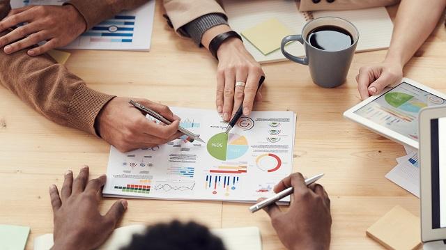 Groep die gedrukte gegevens op een vergadertafel bestudeert voor een dagelijks verkooprapport