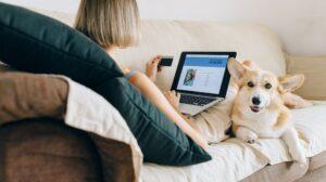 Vrouw die online betaalt terwijl corgi in de buurt rust