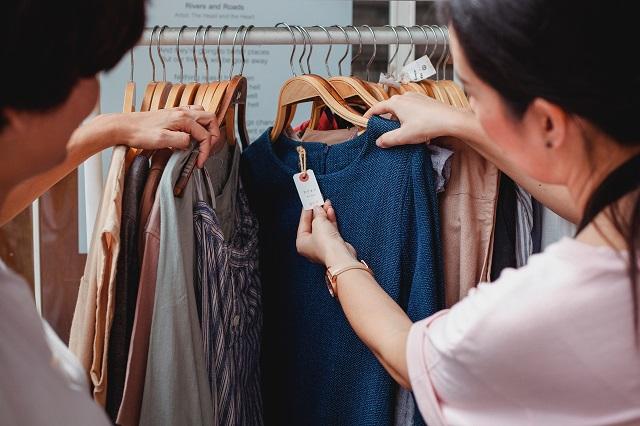 Twee mensen bladeren door een kledingrek in een winkel