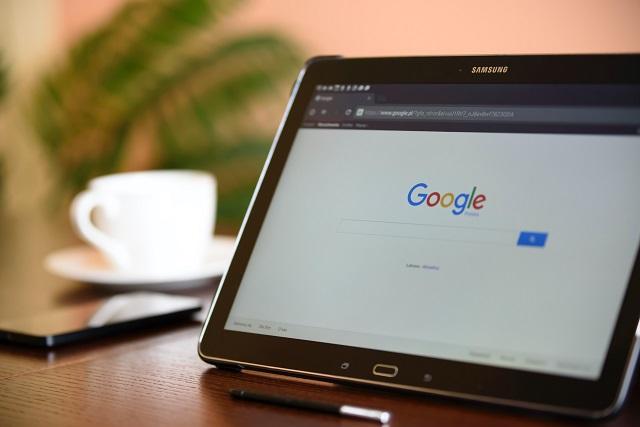 Tablet rustend op een houten tafel met Google-zoekopdracht geopend