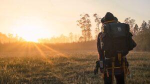 Persoon die door veld en zonsondergang aan het backpacken is