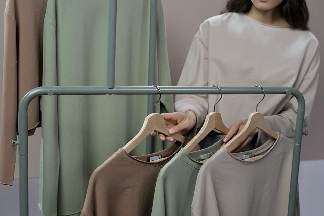 Vrouw sorteert kledingrek