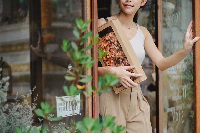 Vrouw verlaat bloemenwinkel met doos