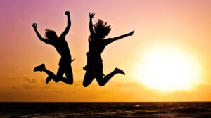 Twee mensen springen op een strand bij zonsondergang